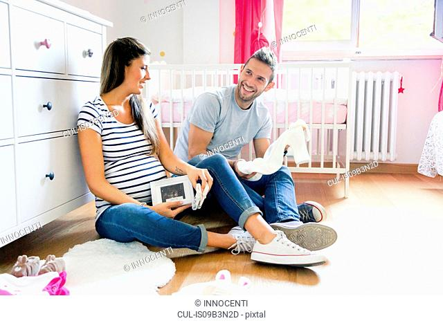 Pregnant couple sitting on floor in nursery preparing baby clothes