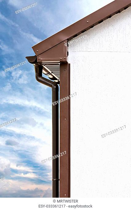 brown PVC downspout on wall against sky background