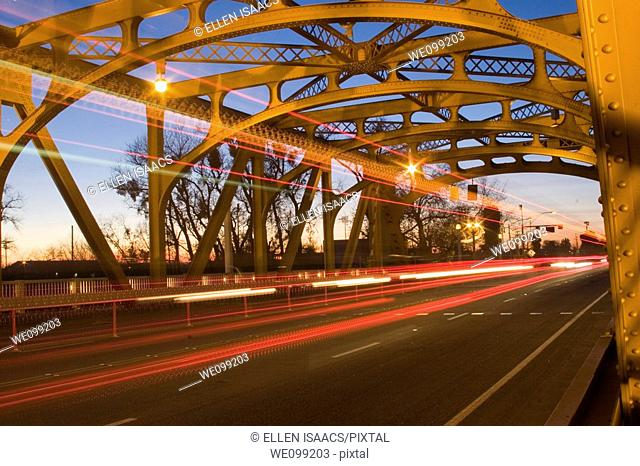 Lights from cars and a bus traveling across the gold steel structure of Tower Bridge at twilight in Sacramento, California  The bridge is a vertical lift bridge...