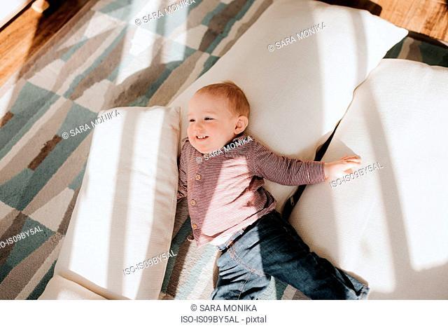 Baby boy lying on cushions on living room floor, overhead view