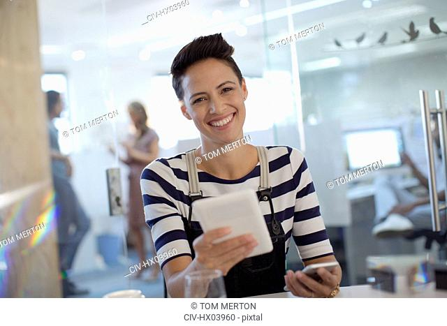 Portrait smiling, confident creative businesswoman using digital tablet in office