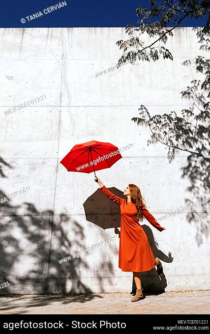 Young woman in red dress holding flying umbrella while standing against tree shadow wall