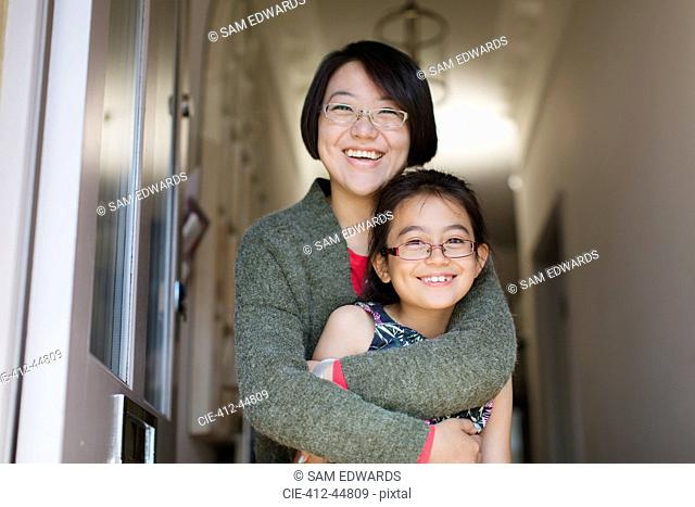Portrait happy, affectionate mother and daughter hugging in doorway
