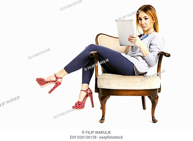 Young woman sitting on a retro chair with tablet reading and watching e-mails