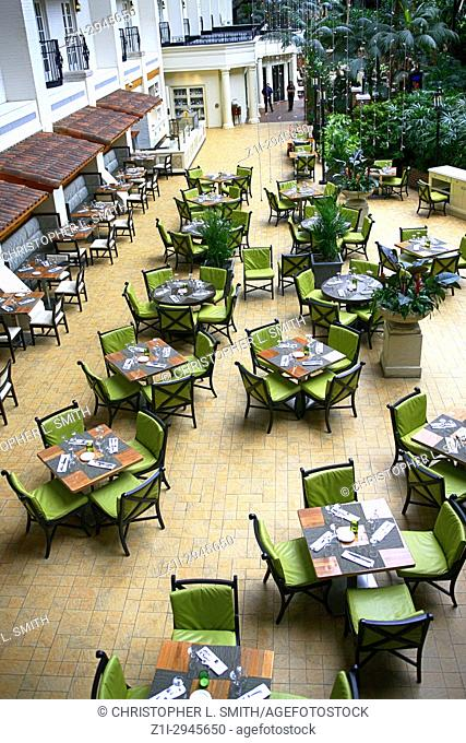 Empty restaurant tables and chairs in the garden style Gaylord Opryland hotel resort in Nashville TN, USA