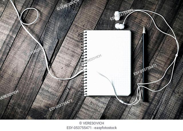 Blank notebook, pencil and headphones on vintage wooden table background. Blank paperwork template for placing your design. Top view