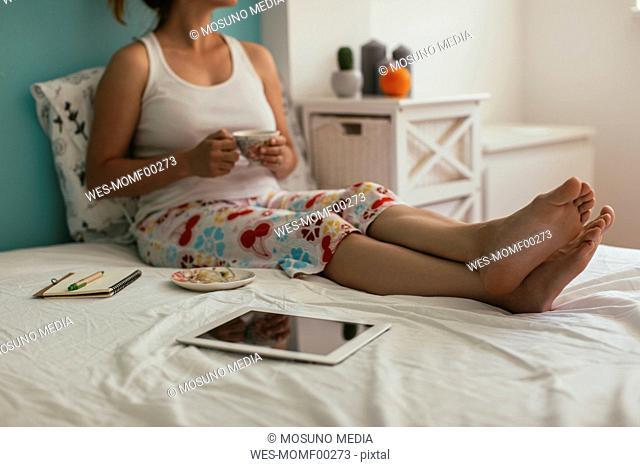 Woman sitting on bed next to tablet drinking coffee