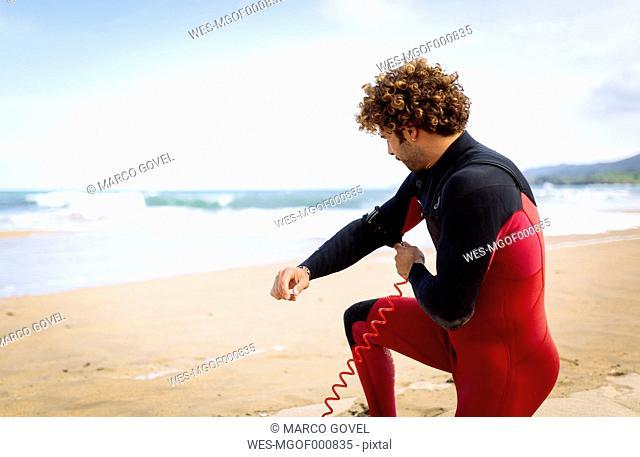 Spain, Asturias, Colunga, surfer preparing on the beach