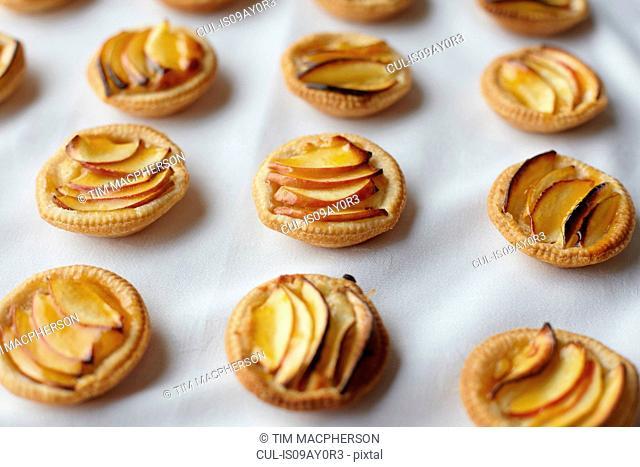 Miniature frangipane apple tarts on tablecloth