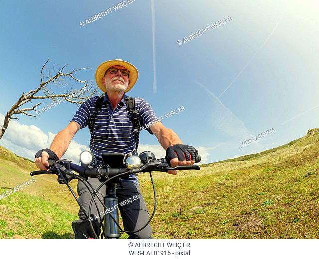 France, Bretagne, Sainte-Anne la Palud, Plage de Treguer, senior man riding mountain e-bike