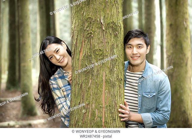Portrait of young smiling couple touching a tree together