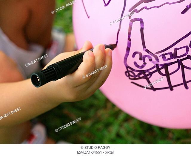 High angle view of a boy drawing on a balloon with a felt tip pen