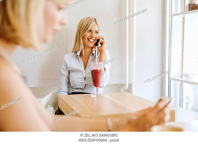 Young women on cell phone in a cafe