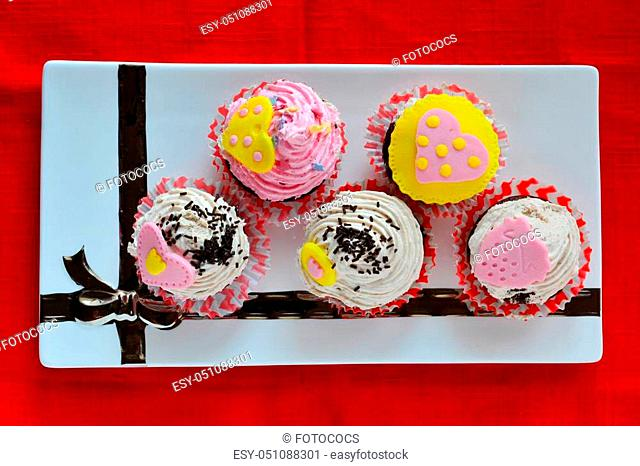 Love muffins, colorful cupcakes decorated with marzipan hearts served in white ceramic saucer, view from above