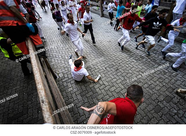 PAMPLONA, SPAIN - JULY 12, 2018: Bulls and people running on the street, encierro, during the festival of San Fermin. Bulls of the cattle ranch of Victoriano...