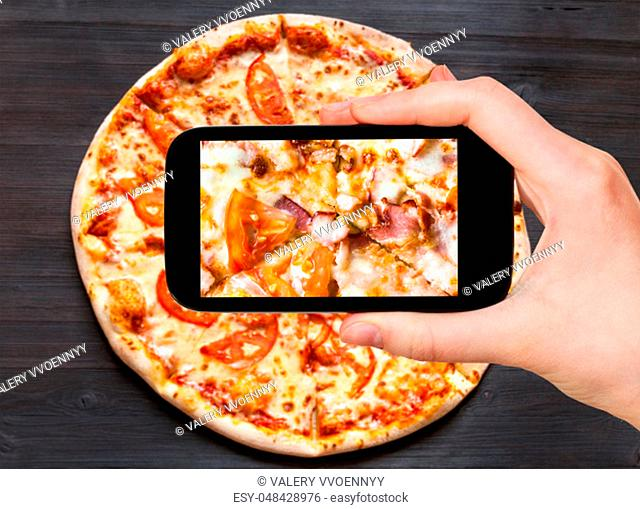 travel concept - visitor photographs of filling of Pizza with Bacon and Tomatoes close up on smartphone