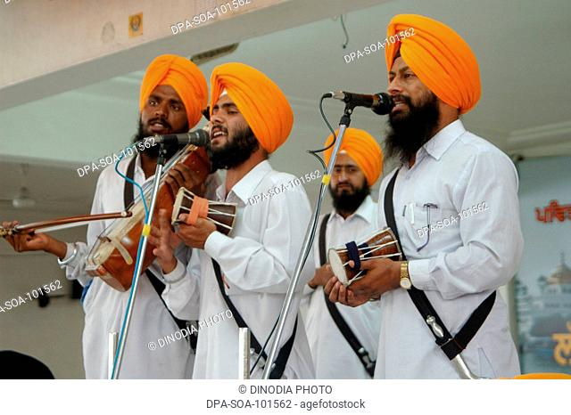 Priests accompanied by musicians in their  continues intonation of the Sri Akhandpath ;nonstop reading of the Gurugranth sahib that goes on for over 70 hours...