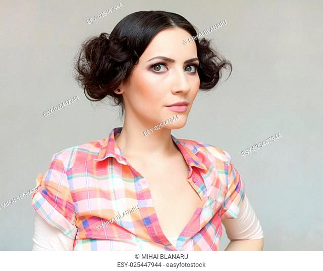 Beautiful sporty woman with two loops of hair dressed in a casual shirt!