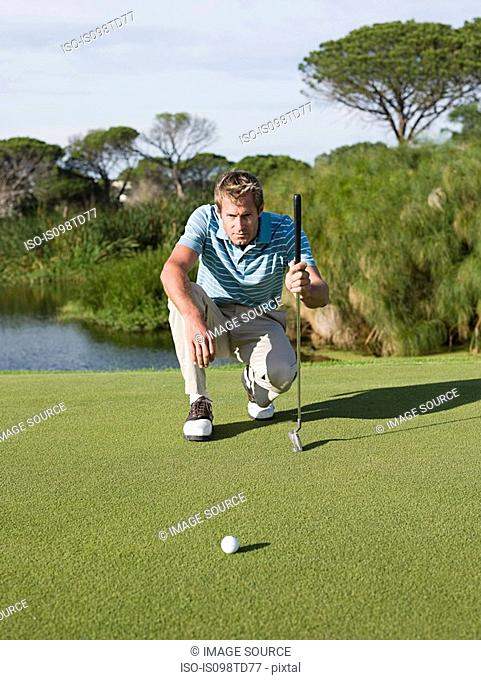 Man playing golf, on putting green