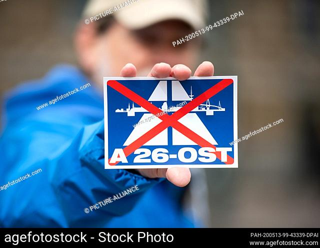 13 May 2020, Hamburg: During a demonstration, an activist from the German Nature and Biodiversity Conservation Union (NABU) holds a sticker with the crossed-out...