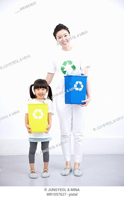 mother and daughter holding a plastic basket with recycling symbol