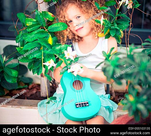 Portrait of a cute girl sitting ouddoor with ukulele