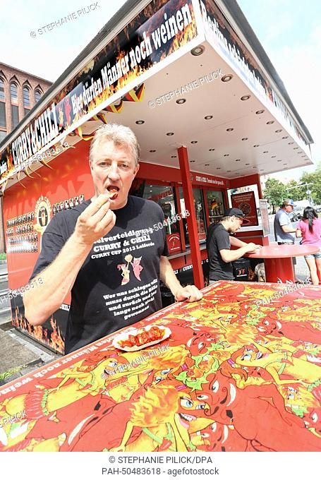 Frank Spiess, owner of the diner 'Curry & Chily', eats a currywurst at his diner in Wedding in Berlin, Germany, 07 July 2014
