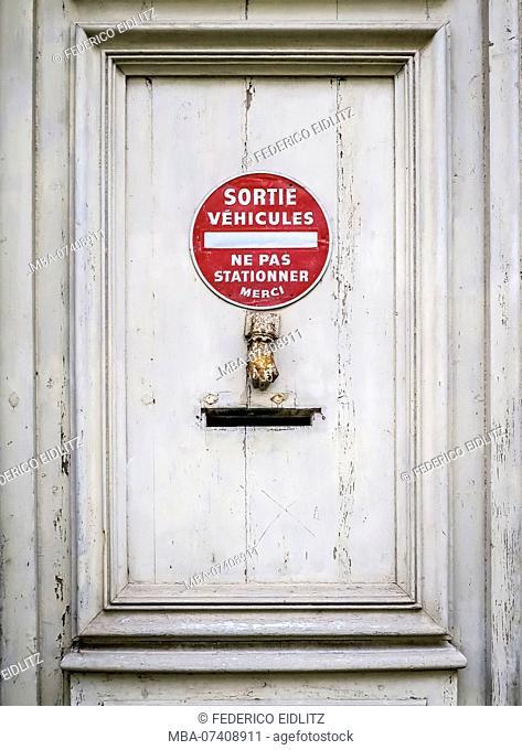 Old wooden door with mailbox and door knocker in Narbonne
