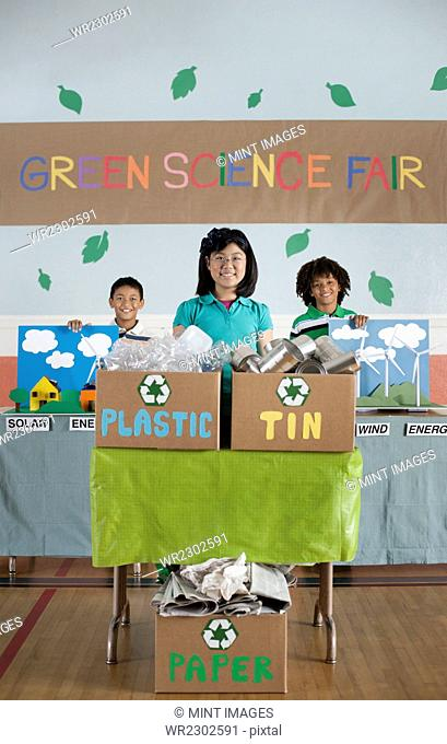 Three children standing behind presentations at the Green Science Fair