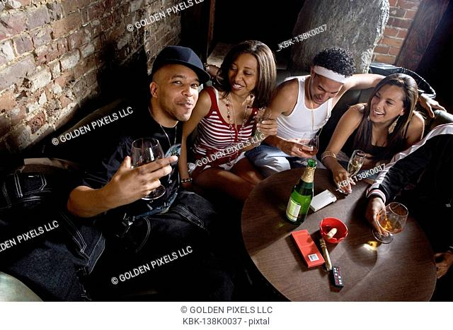 Young men and women in hip-hop fashion partying at a bar