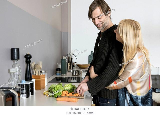 Affectionate mature couple cooking food together in kitchen
