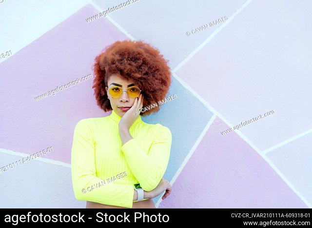 portrait of gorgeous woman with afro hair and yellow sweater over pink wall