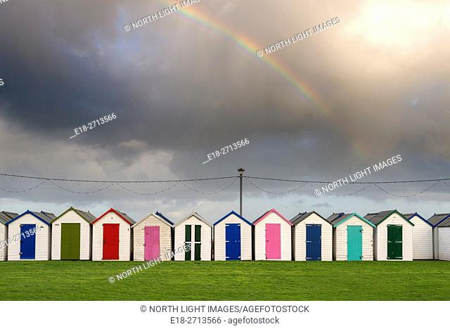 UK, England, Devonshire, Paignton. A rainbow in the sky above colourful beachside changing huts on the south coast of England