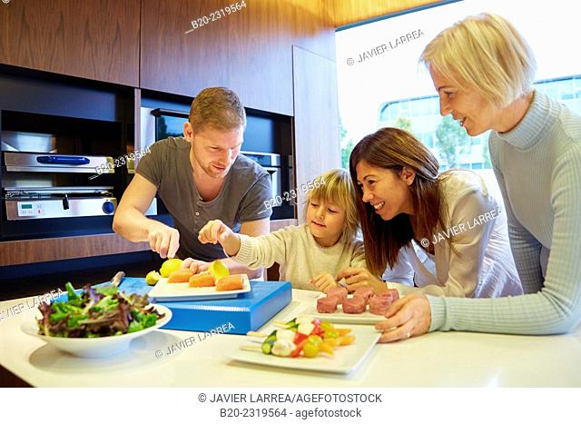 Family in the kitchen. Three generations. Healthy eating. Healthy growth. Vegetables and fish