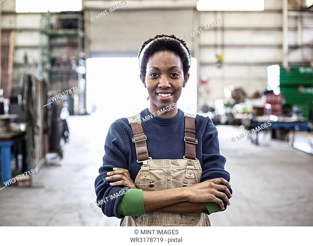Black woman factory worker wearing coveralls in a large sheet metal factory