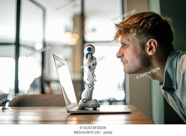 Man looking at toy robot, standing on his laptop