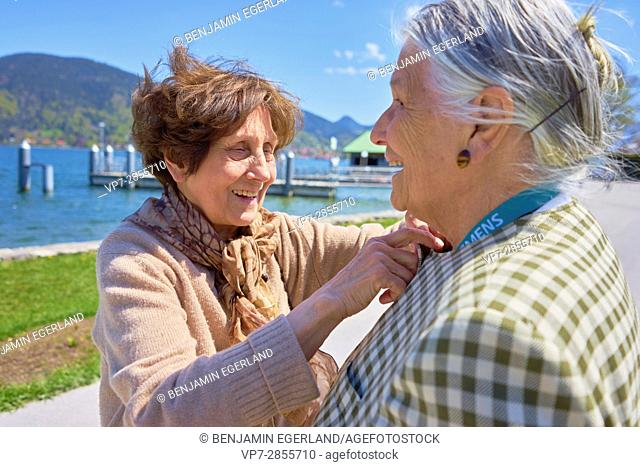 Two old friends laughing at seaside while caring about each other