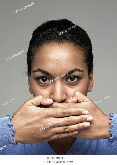 Young woman covering mouth with hands