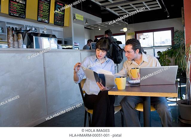 Businessman and a businesswoman reading a document