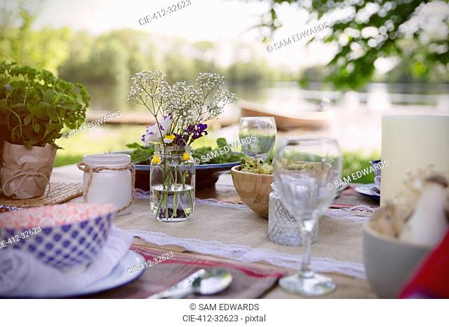 Place settings and simple bouquet on garden party table at lakeside
