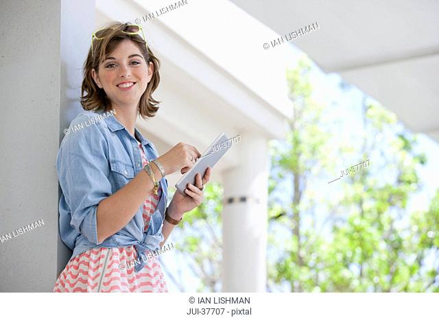 Portrait of smiling young woman using digital tablet