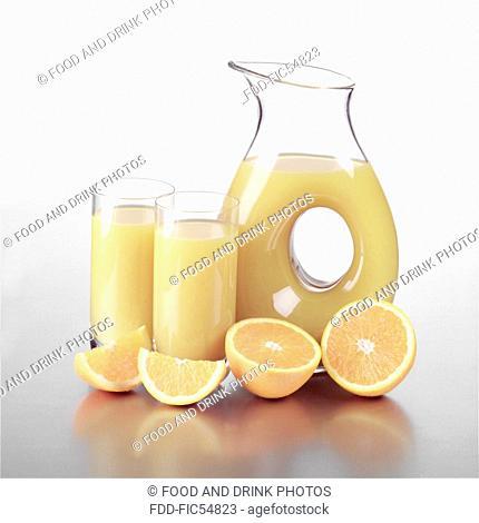 Jug of Orange Juice with two glasses and orange slices
