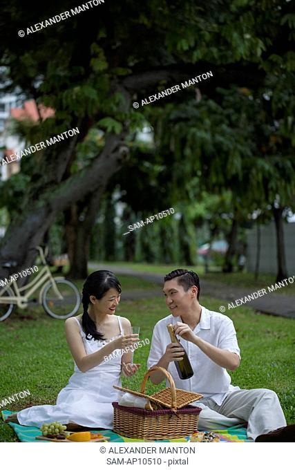 Singapore, Couple on picnic blanket opening wine