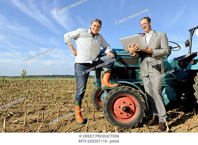 Farmer and businessman talking to each other, Bavaria, Germany