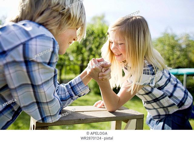 Siblings arm wrestling on wooden table in back yard
