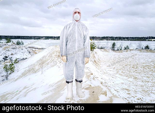 Man wearing protective suit and mask standing in rural winter landscape