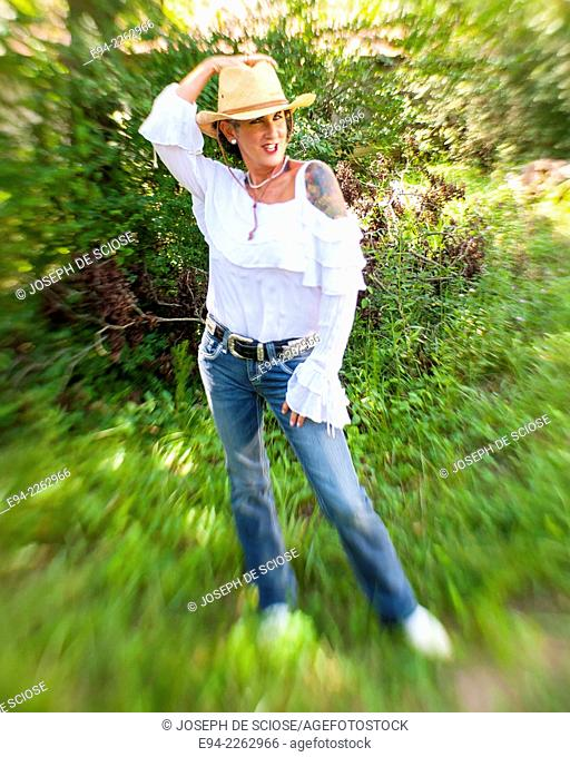 54 year old brunette woman with tattoos in outdoor setting wearing a straw hat and blue jeans looking at the camera