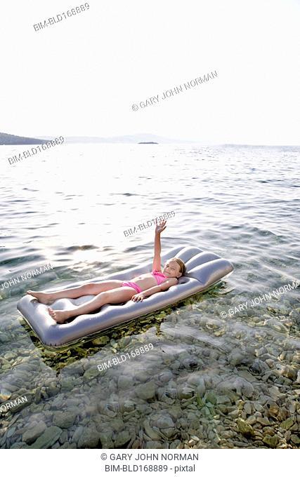Caucasian girl floating on raft in lake