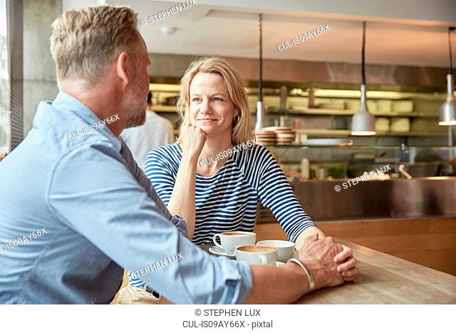 Mature couple in coffee shop holding hands chatting