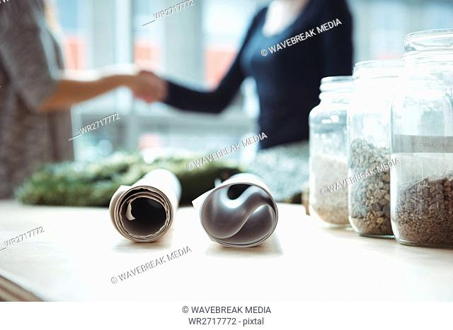 Sample of pebbles in jar and blueprint on table